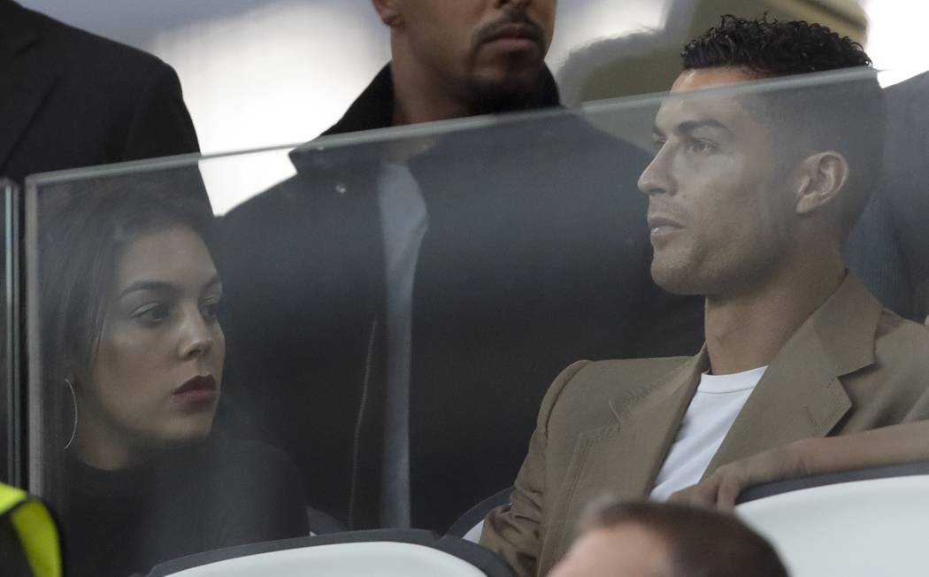 Juventus forward Cristiano Ronaldo and his partner Georgina sit in the stands prior to the Champions League, group H soccer match between Juventus and Young Boys, at the Allianz stadium in Turin, ...