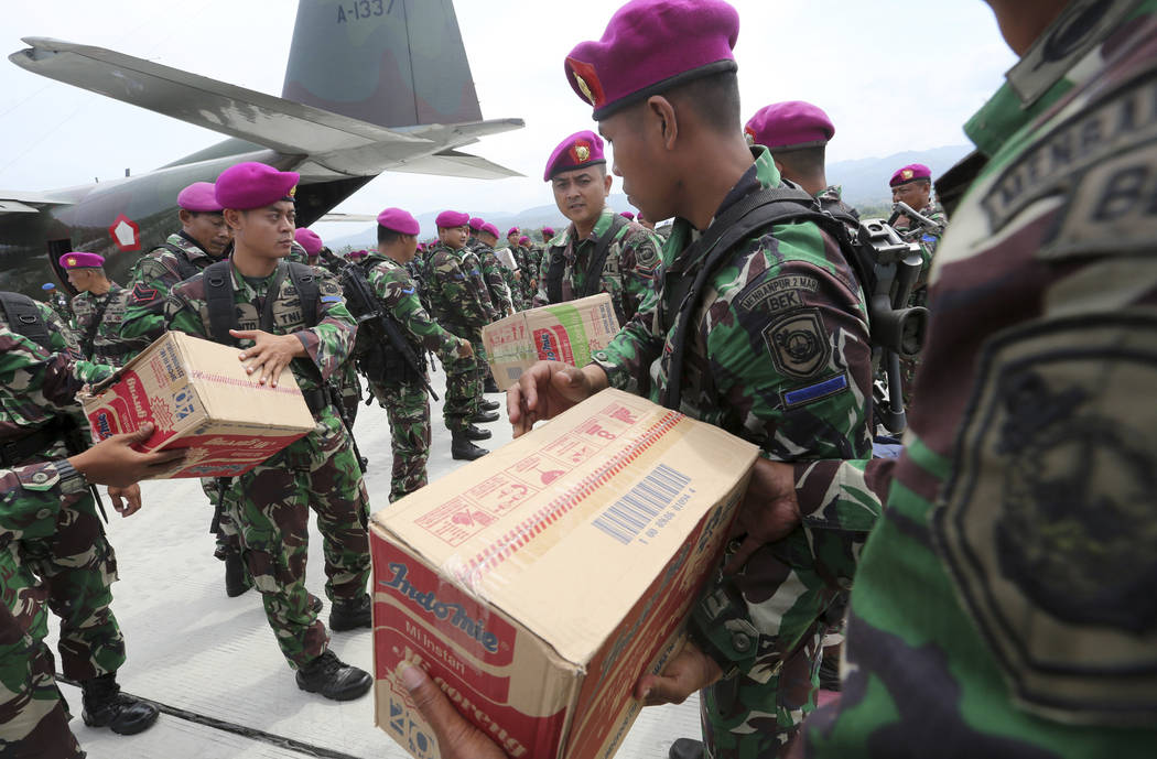 Indonesian military personnel distribute relief aid at the Mutiara Sis Al-Jufri airport to evacuate the earthquake and tsunami-damaged city of Palu, Central Sulawesi Indonesia, Thursday, Oct. 4, 2 ...