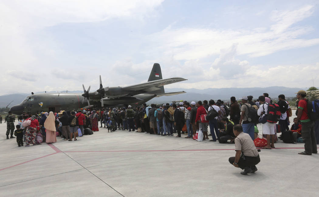 People line up to board an Air Force cargo plane at the Mutiara Sis Al-Jufri airport to evacuate the earthquake and tsunami-damaged city of Palu, Central Sulawesi Indonesia, Thursday, Oct. 4, 2018 ...