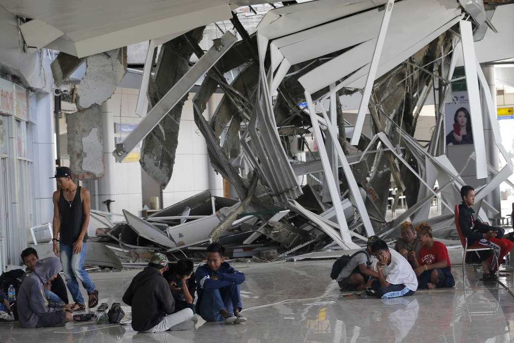 People sit outside Mutiara Sis Al-Jufri airport damaged by a powerful earthquake and tsunami in Palu, Central Sulawesi Indonesia, Thursday, Oct. 4, 2018. Life is on hold for thousands living in te ...