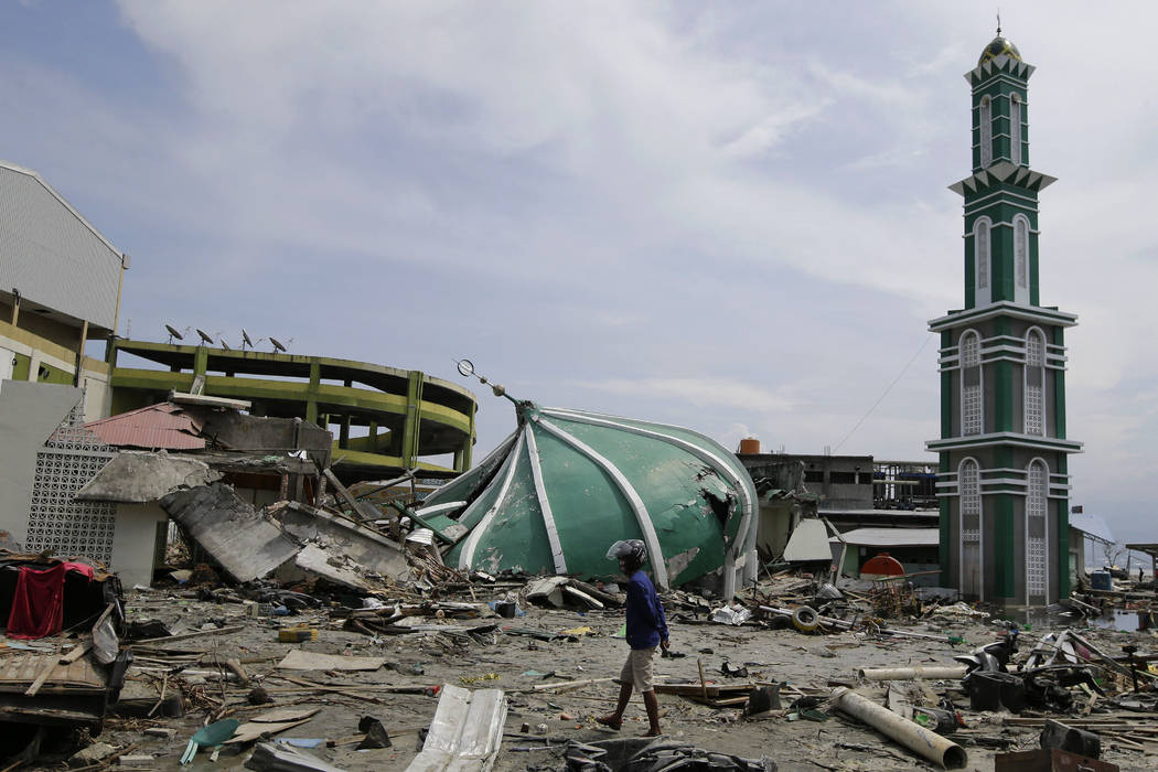 A man walks past the remains of a mosque after it was destroyed in the massive earthquake and tsunami that hit Palu, Central Sulawesi, Indonesia Thursday, Oct. 4, 2018. Life is on hold for thousan ...