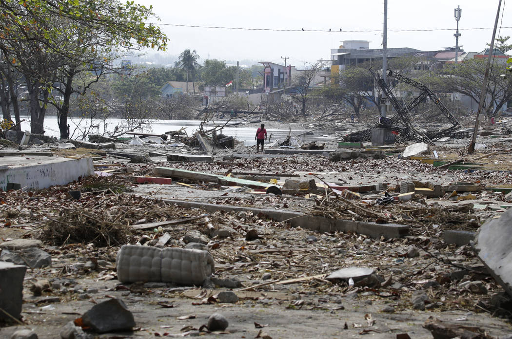 A man walks past the remains of structures at a park after it was destroyed in the massive earthquake and tsunami that hit Palu, Central Sulawesi, Indonesia Thursday, Oct. 4, 2018. Life is on hold ...