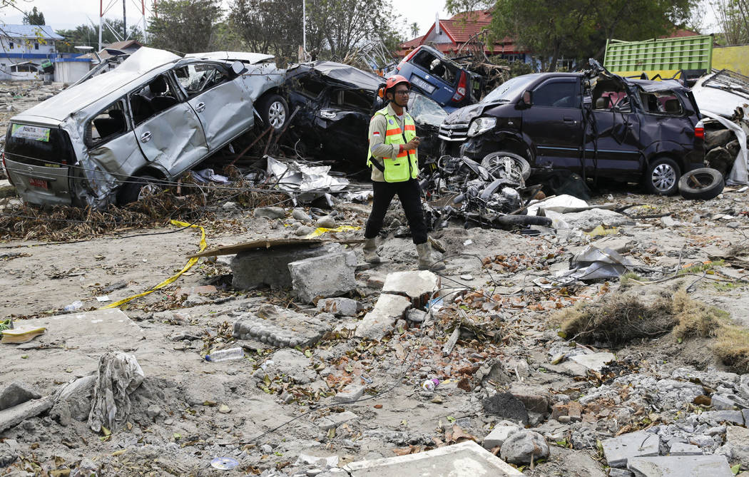 A man walks past remains of cars that were destroyed in the massive earthquake and tsunami that hit Palu, Central Sulawesi, Indonesia Thursday, Oct. 4, 2018. Life is on hold for thousands living i ...