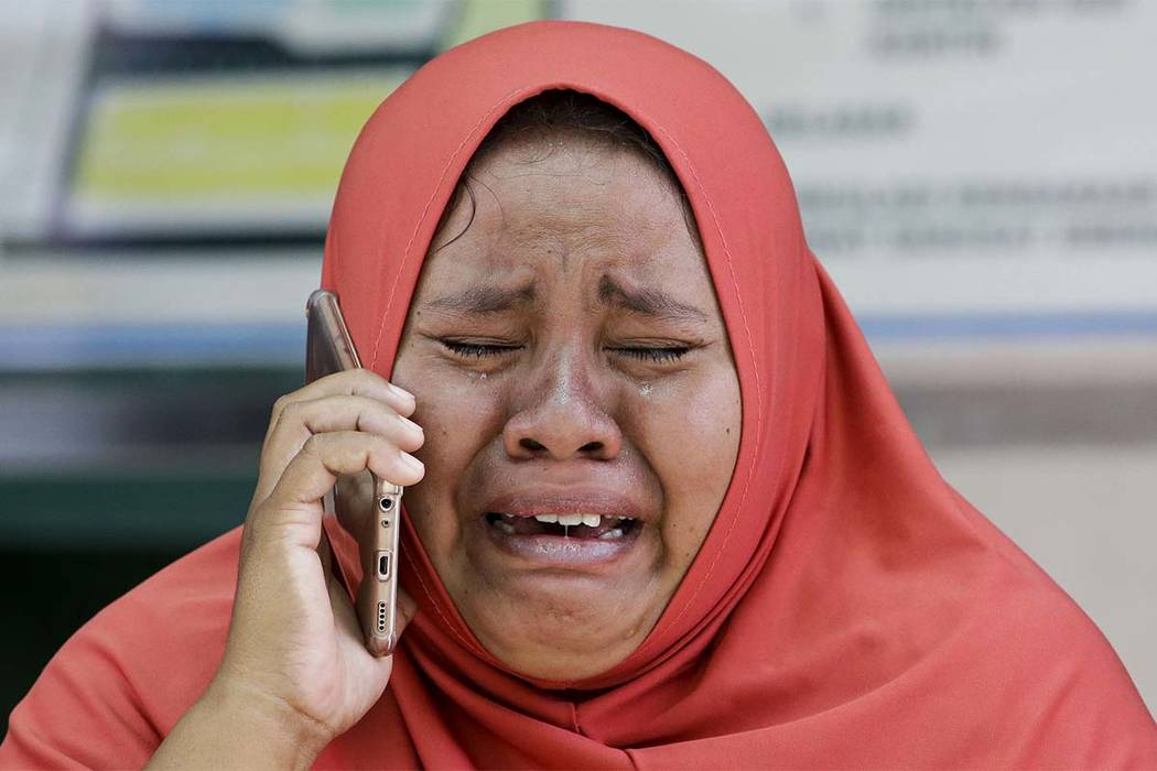 A woman cries as she uses the recovered mobile phone of her daughter who was killed in the massive earthquake at Palu, Central Sulawesi, Indonesia Thursday, Oct. 4, 2018. The mother did not get th ...
