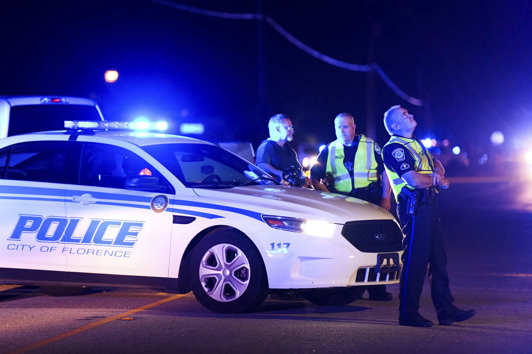 Authorities direct traffic on Hoffmeyer Road near the Vintage Place neighborhood where several law enforcement officers were shot, one fatally, Wednesday, Oct. 3, 2018, in Florence, S.C. (AP Photo ...