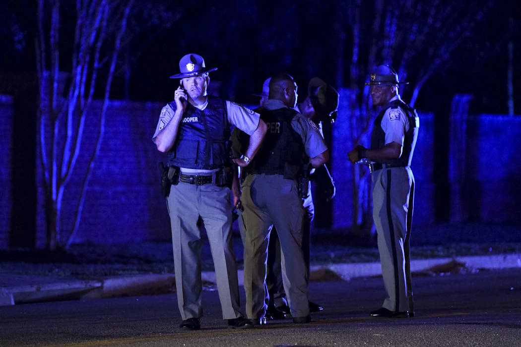 South Carolina state troopers gather on Hoffmeyer Road near the Vintage Place neighborhood where several law enforcement officers were shot, one fatally, Wednesday, Oct. 3, 2018, in Florence, S.C. ...