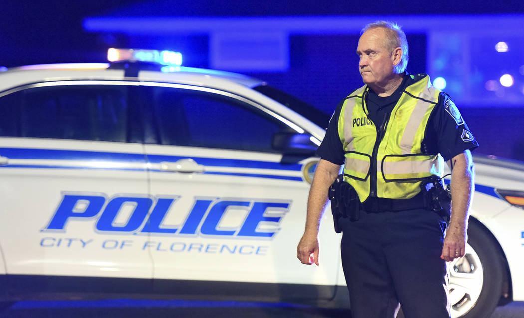 A police officer directs traffic on Hoffmeyer Road near the Vintage Place neighborhood where three deputies and two city officers were shot Wednesday, Oct. 3, 2018, in Florence, S.C. (AP Photo/Sea ...