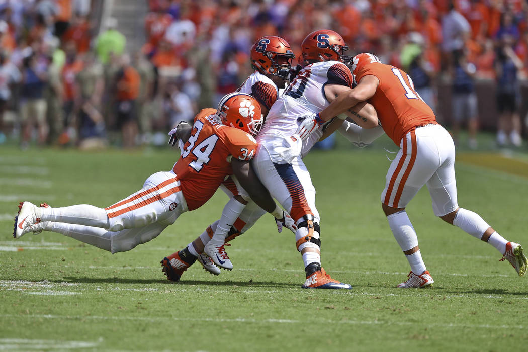 Clemson's Kendall Joseph (34) tackles Syracuse's Sean Riley while Riley's teamamte Airon Servais blocks Tanner Muse during the first half of an NCAA college football game against Syracuse Saturday ...