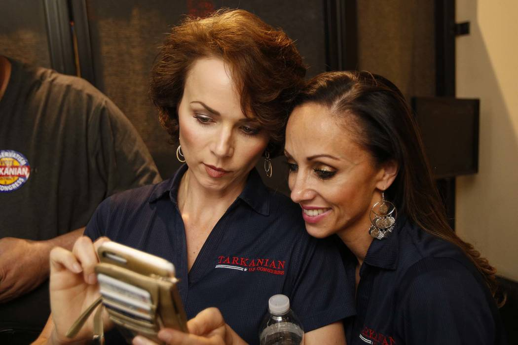 Amy Tarkanian, left, wife of Republican 3rd Congressional District candidate Danny Tarkanian, and her friend Jamie Brashaw check for campaign result updates during Danny Tarkanian's election night ...