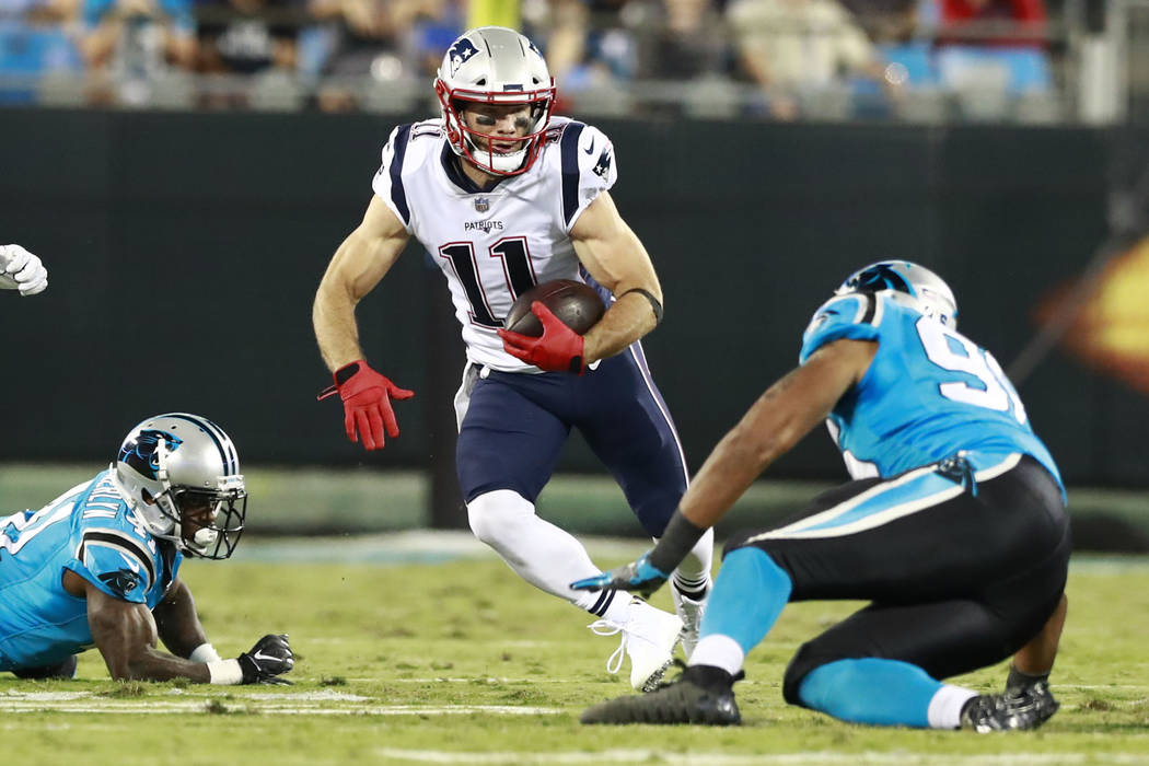New England Patriots' Julian Edelman (11) runs as Carolina Panthers' Wes Horton (96) defends during the first half of a preseason NFL football game in Charlotte, N.C., Friday, Aug. 24, 2018. (AP P ...