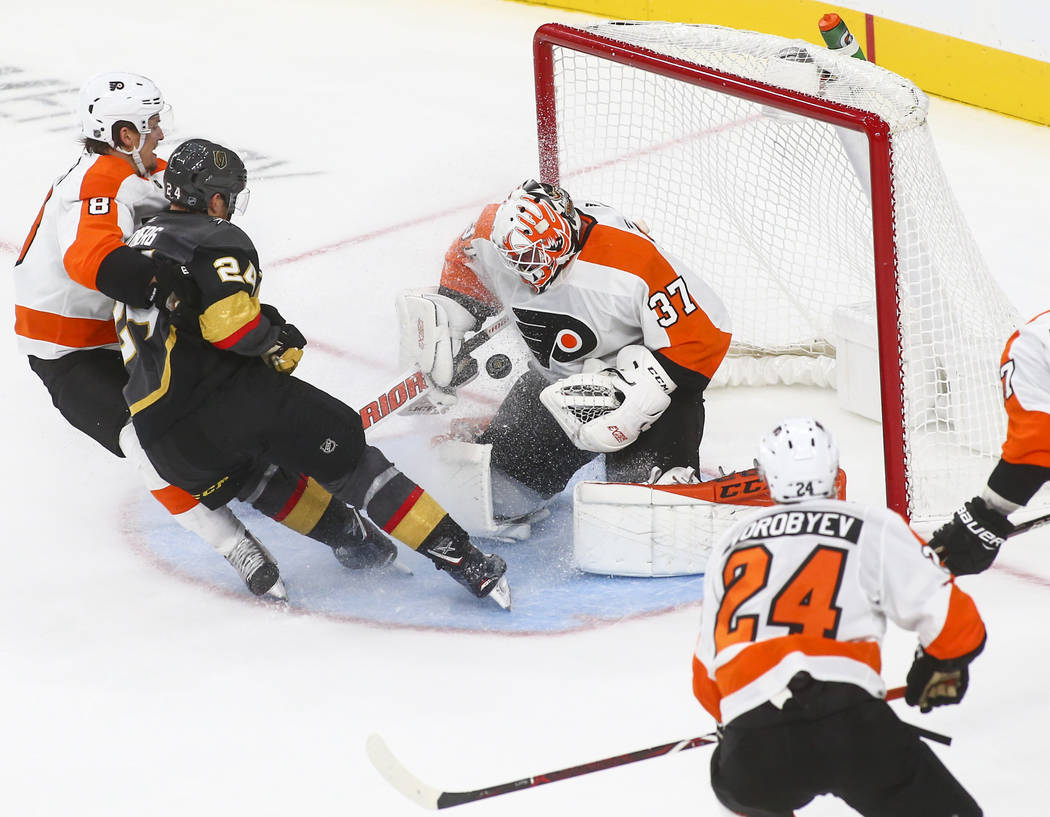 Philadelphia Flyers goaltender Brian Elliott (37) blocks a shot from Golden Knights center Oscar Lindberg (24) during the third period of a season-opening game at T-Mobile Arena in Las Vegas on Th ...