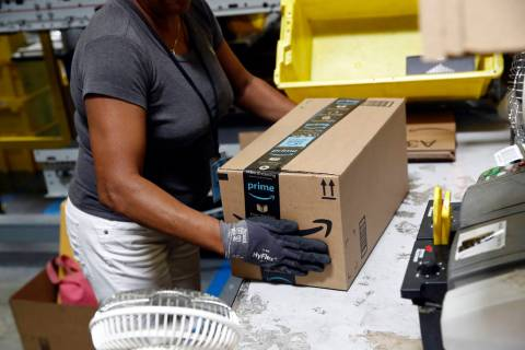 Myrtice Harris applies tape to a package before shipment at an Amazon fulfillment center in Bal ...
