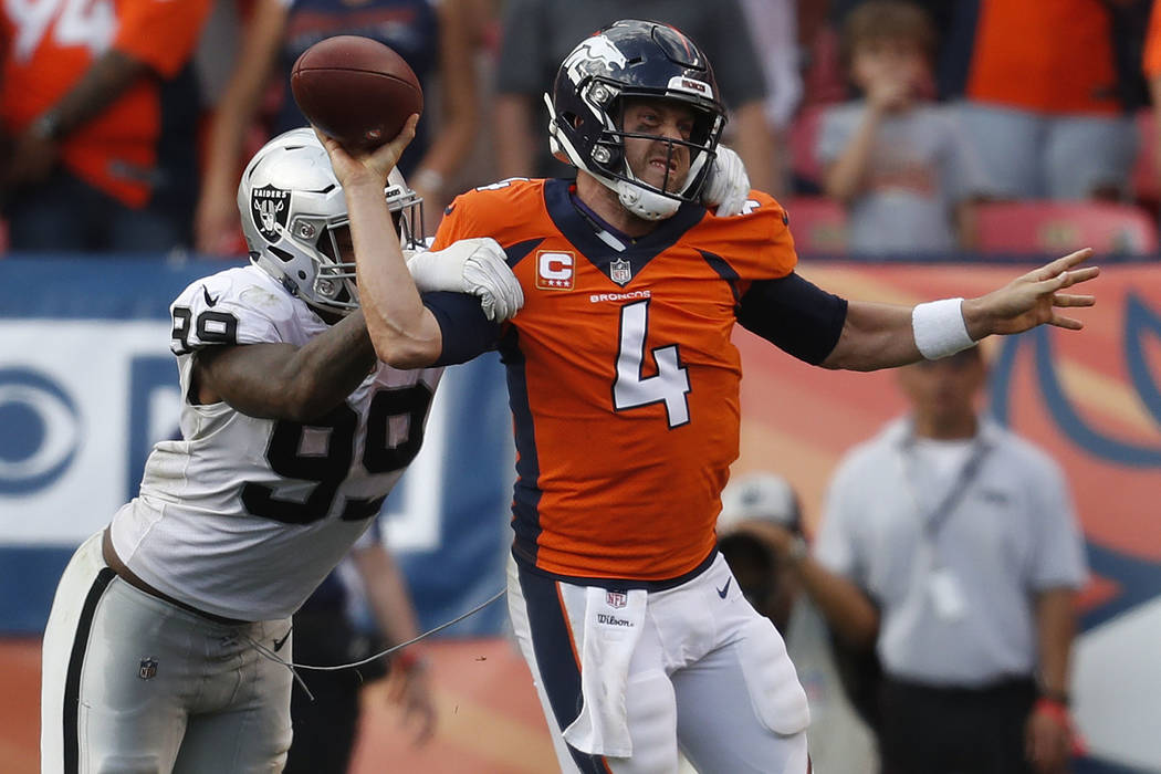 Denver Broncos quarterback Case Keenum (4) is pressured by Oakland Raiders defensive end Arden Key (99) during the second half of an NFL football game, Sunday, Sept. 16, 2018, in Denver. The Bronc ...