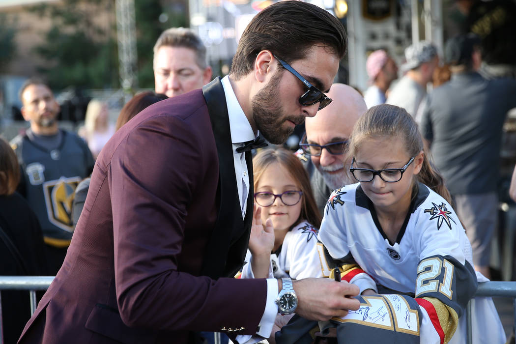 Vegas Golden Knights right wing Alex Tuch (89) signs an autograph for Rebecca Staskin, 10, far right ,with his sister Emma, 7, and father Michael of Las Vegas, before the Vegas Golden Knights seas ...