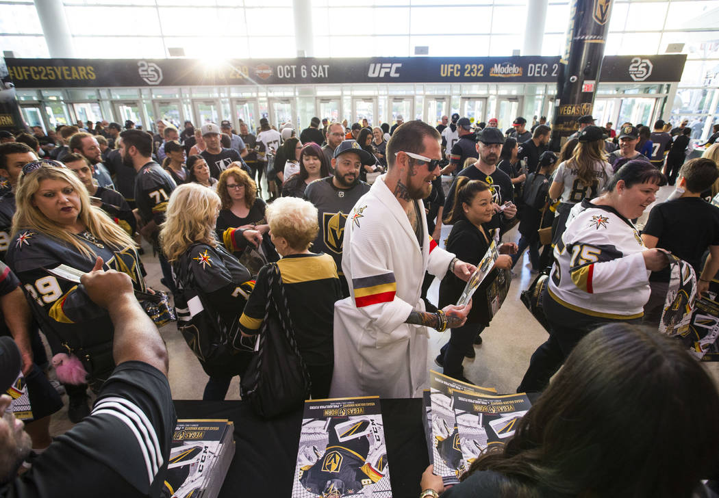 A hockey fan in a Golden Knights themed bath robe gets a poster before the Golden Knights take on the Philadelphia Flyers in their season-opening game at T-Mobile Arena in Las Vegas on Thursday, O ...