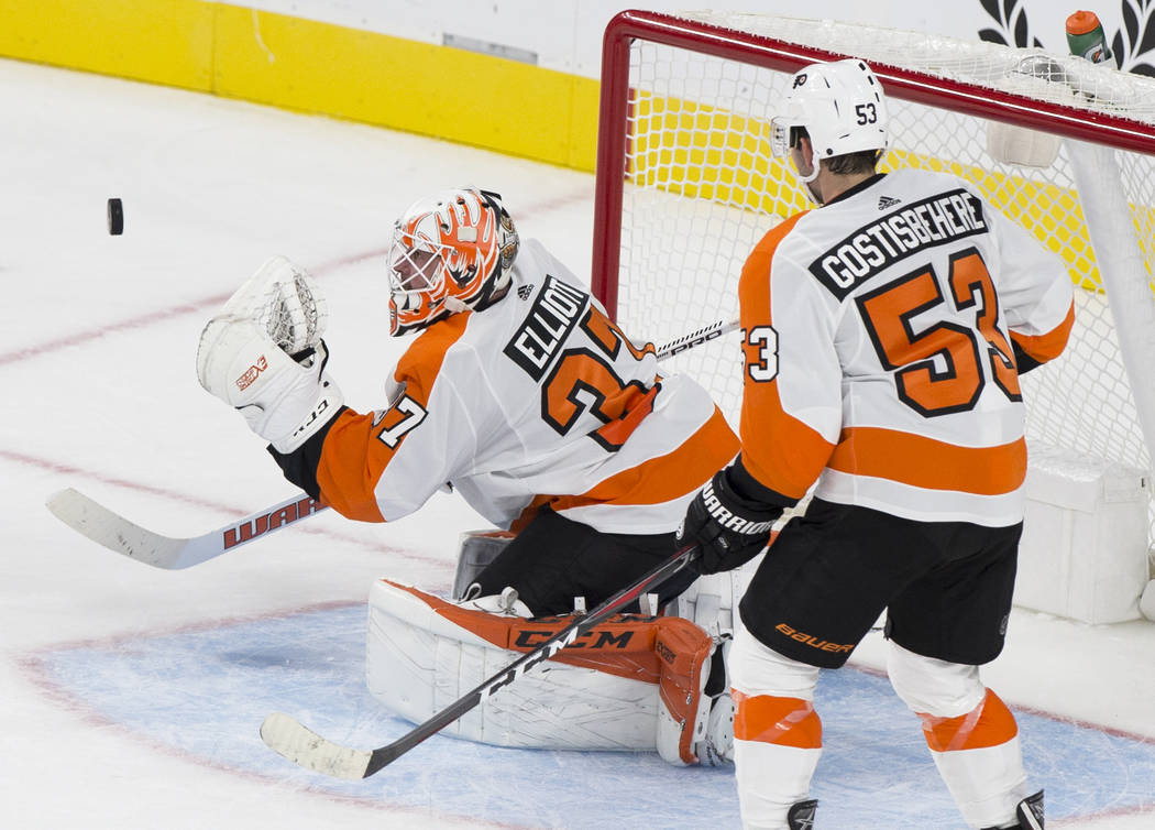 Philadelphia Flyers goaltender Brian Elliott (37) makes a second period save with the help of defenseman Shayne Gostisbehere (53) during their NHL hockey game with the Golden Knights on Thursday, ...