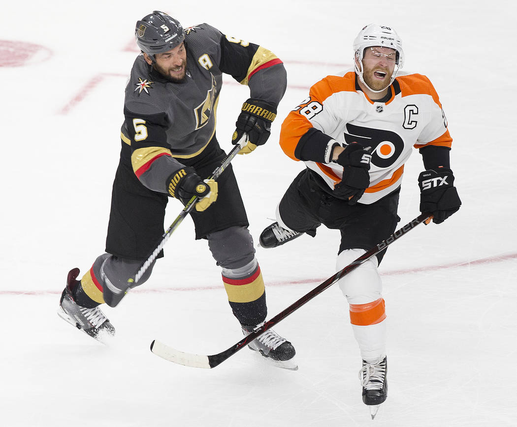 Golden Knights defenseman Deryk Engelland (5) collides with Philadelphia Flyers defenseman Robert Hagg (8) in the second period during their NHL hockey game on Thursday, Oct. 4, 2018, at T-Mobile ...