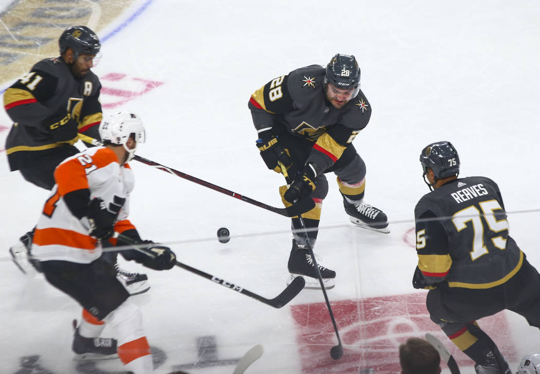 Golden Knights left wing William Carrier (28) battles for the puck against Philadelphia Flyers center Scott Laughton (21) alongside Golden Knights' Ryan Reaves (75) and Pierre-Edouard Bellemare (4 ...
