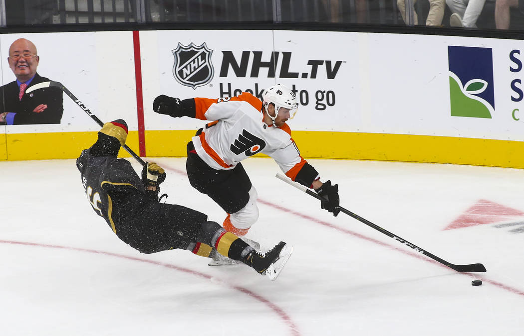 Golden Knights defenseman Colin Miller (6) gets tripped up by Philadelphia Flyers left wing Michael Raffl (12) during the second period of a season-opening game at T-Mobile Arena in Las Vegas on T ...