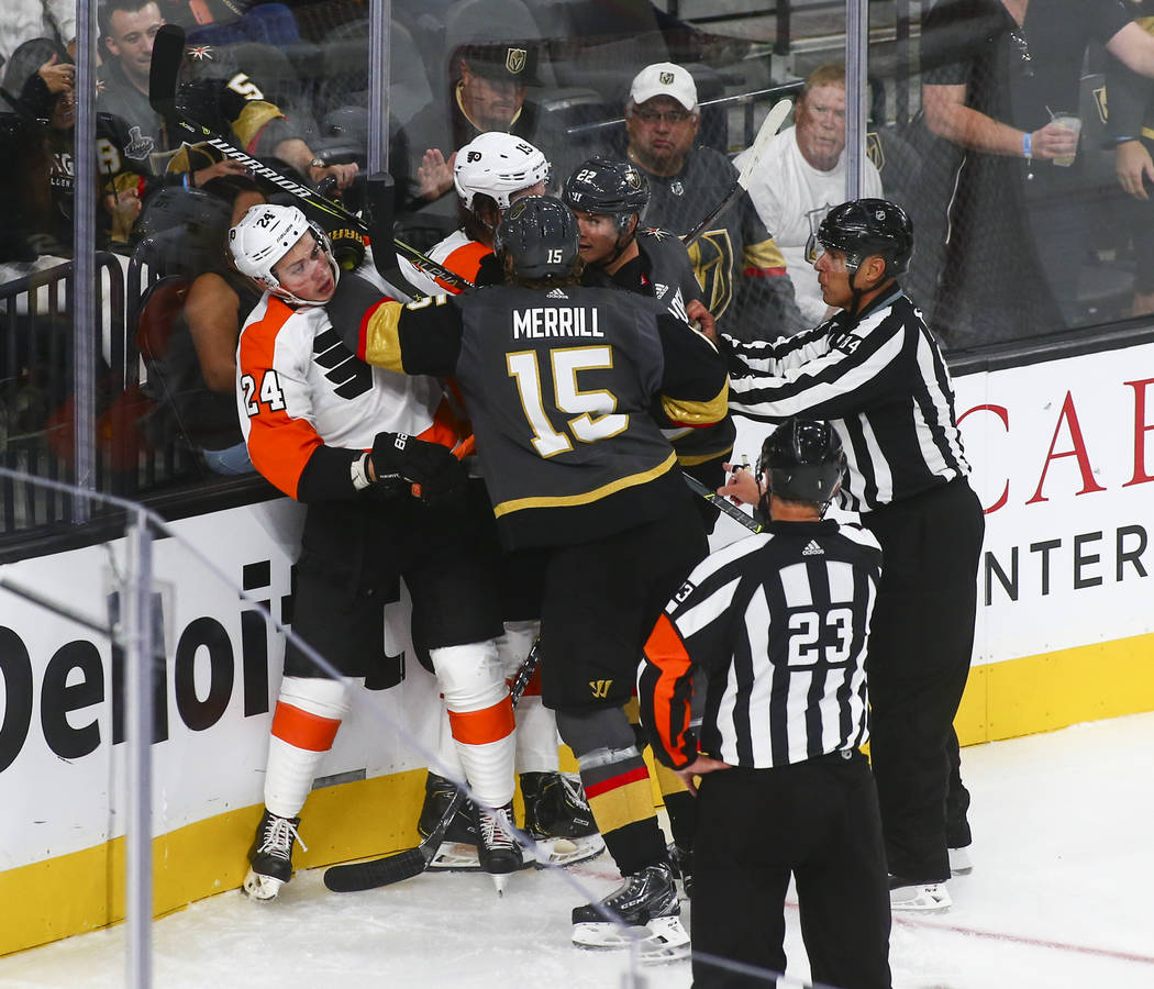 Golden Knights defensemen Jon Merrill (15) and Nick Holden (22) fight Philadelphia Flyers' Mikhail Vorobyev (24) and Nolan Patrick (19) during the third period of a season-opening game at T-Mobile ...