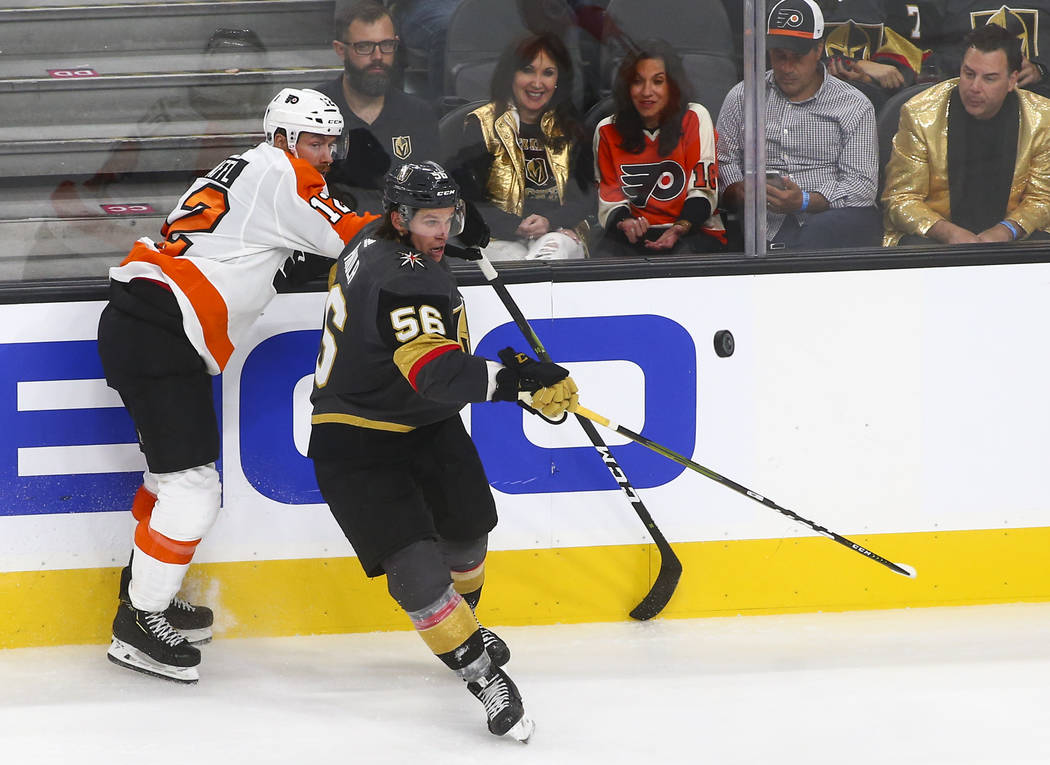 The puck flies in front of Philadelphia Flyers left wing Michael Raffl (12) and Golden Knights left wing Erik Haula (56) during the third period of a season-opening game at T-Mobile Arena in Las V ...