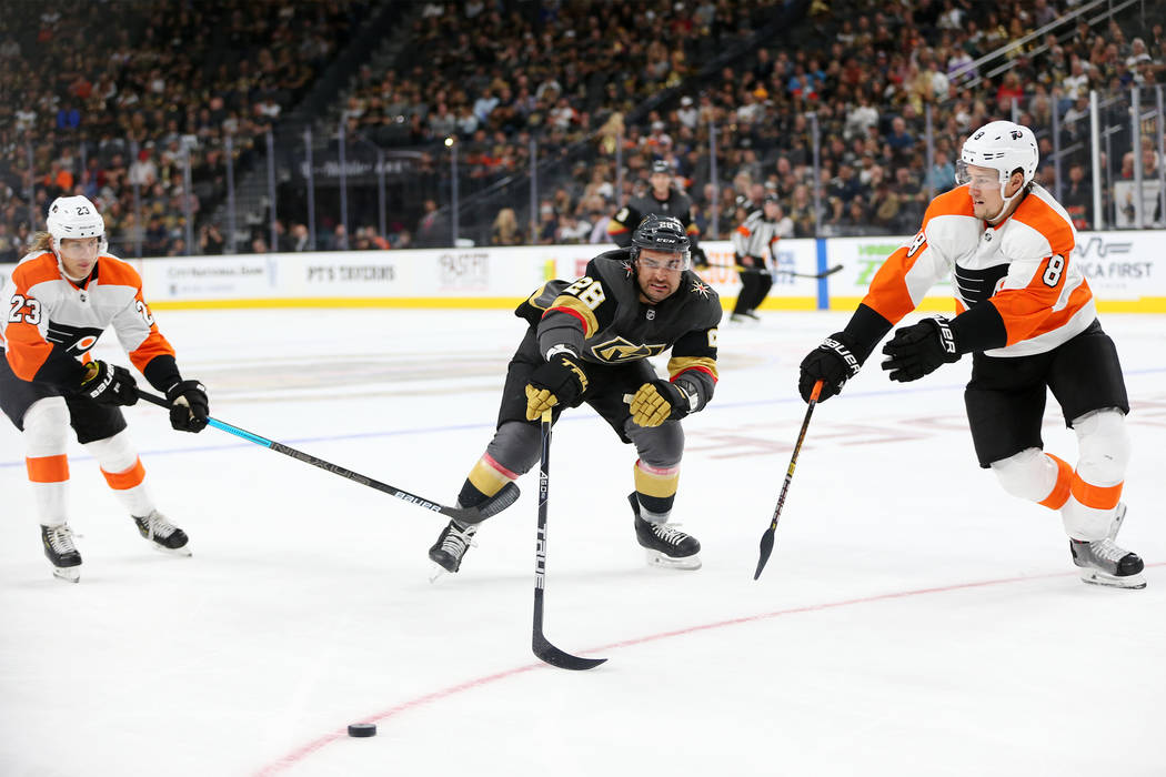 Vegas Golden Knights left wing William Carrier (28) goes for the puck under pressure from Philadelphia Flyers left wing Oskar Lindblom (23) and defenseman Robert Hagg (8) in the third period of a ...