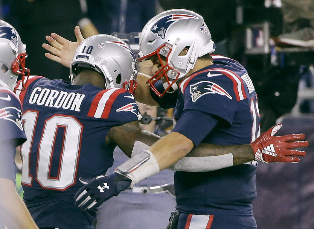 New England Patriots quarterback Tom Brady, right, celebrates his touchdown pass to wide receiver Josh Gordon (10) during the second half of an NFL football game against the Indianapolis Colts, Th ...