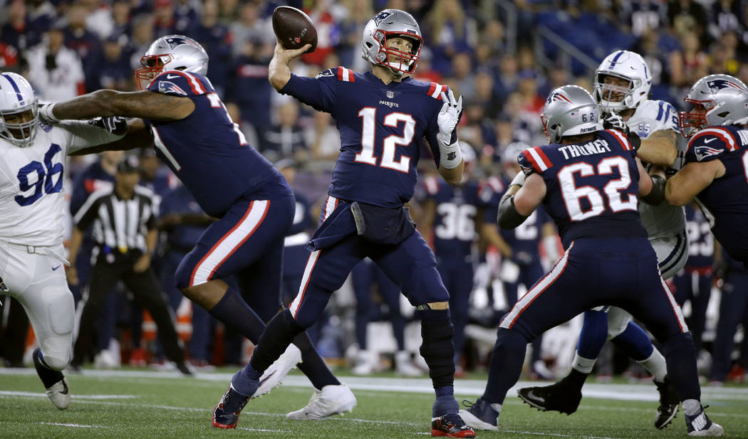 New England Patriots quarterback Tom Brady (12) passes under pressure from the Indianapolis Colts during the first half of an NFL football game, Thursday, Oct. 4, 2018, in Foxborough, Mass. (AP Ph ...