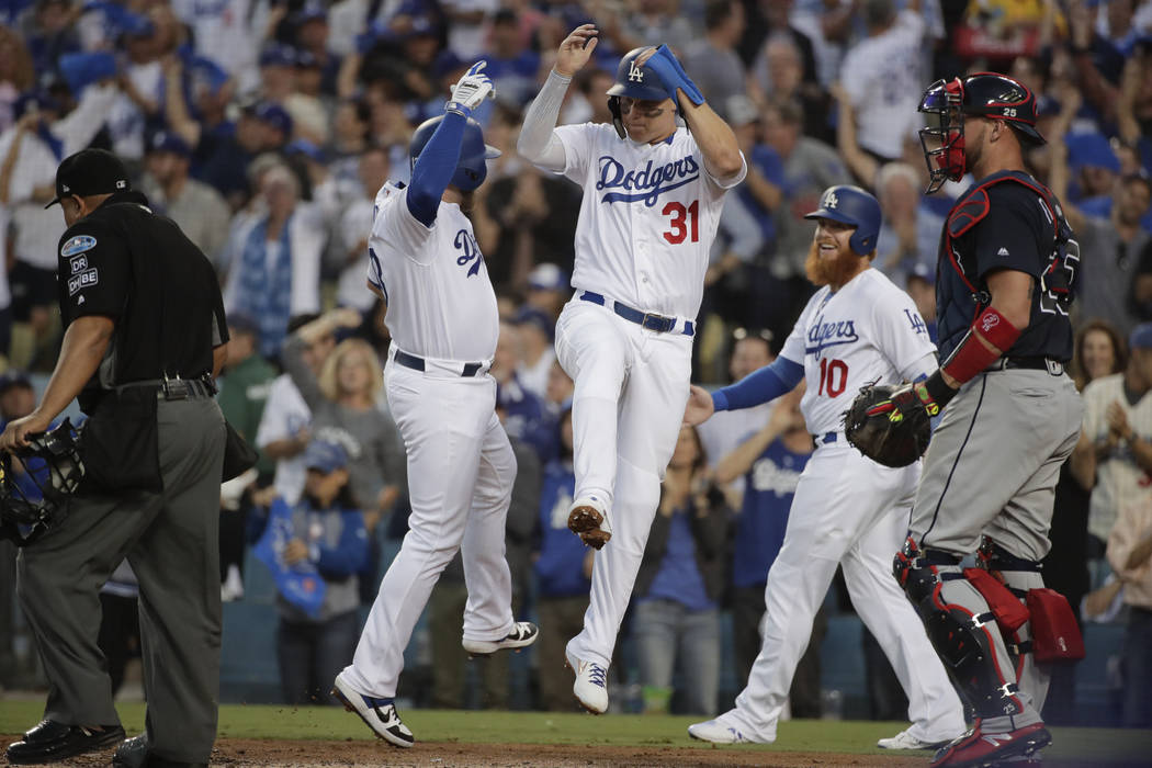 Los Angeles Dodgers' Max Muncy, left, celebrates his three-run home with Joc Pederson, center, and Justin Turner during the second inning of Game 1 of the National League Division Series against t ...