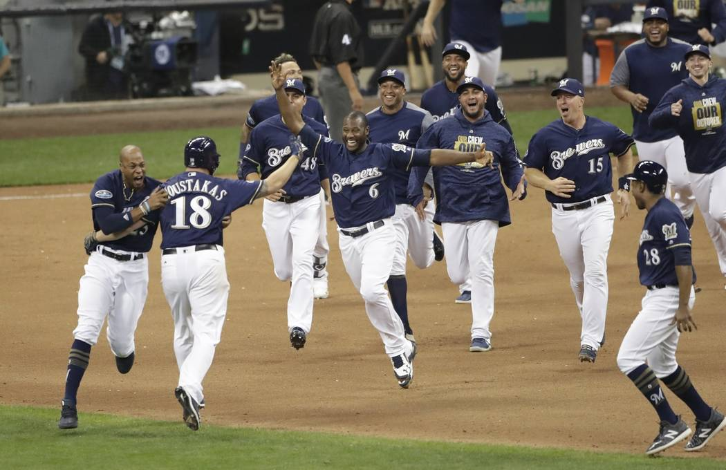 Milwaukee Brewers' Mike Moustakas reacts after hitting a walk off RBI single during the 10th inning of Game 1 of the National League Divisional Series baseball game against the Colorado Rockies Th ...