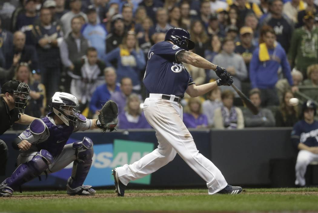 Milwaukee Brewers' Mike Moustakas hits a walk off RBI single during the 10th inning of Game 1 of the National League Divisional Series baseball game against the Colorado Rockies Thursday, Oct. 4, ...