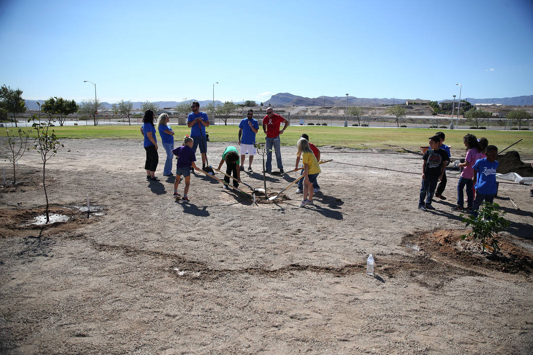 Volunteers including students help plant trees at Forbuss Elementary School in Las Vegas as part of United Way of Southern Nevada's third annual Day of Caring, Friday, Oct. 5, 2018. Erik Verduzco ...