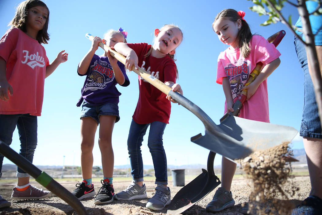Volunteers including students from left, Kai Peterson, 7, Brooklyn Zirkel, 6, Skyelynn Traufler, 5, Madison Palmer, 6, help plant a tree at Forbuss Elementary School in Las Vegas as part of United ...