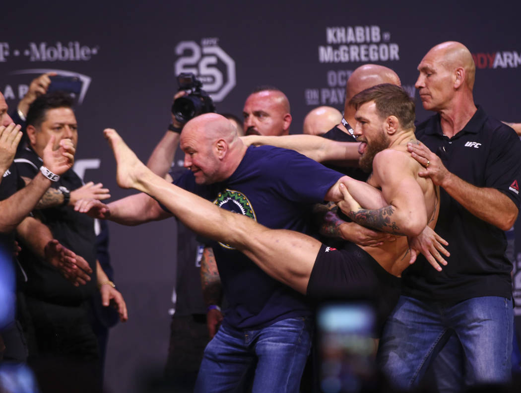 Conor McGregor tries to kick Khabib Nurmagomedov, out of frame to the left, while facing off during the ceremonial weigh-in event ahead of UFC 229 at T-Mobile Arena in Las Vegas on Friday, Oct. 5, ...