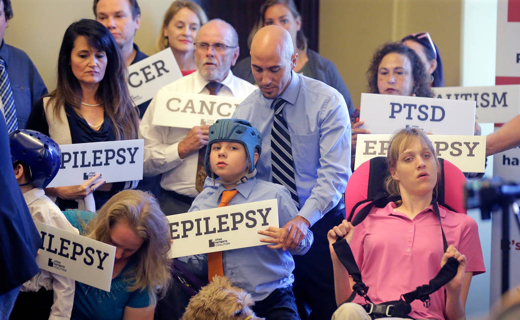 Davis Cromar, center, holds his son Holden, 10, who suffers from epilepsy, while standing with other patients, caregivers and supporters during the Utah Patients Coalition news conference, in Salt ...