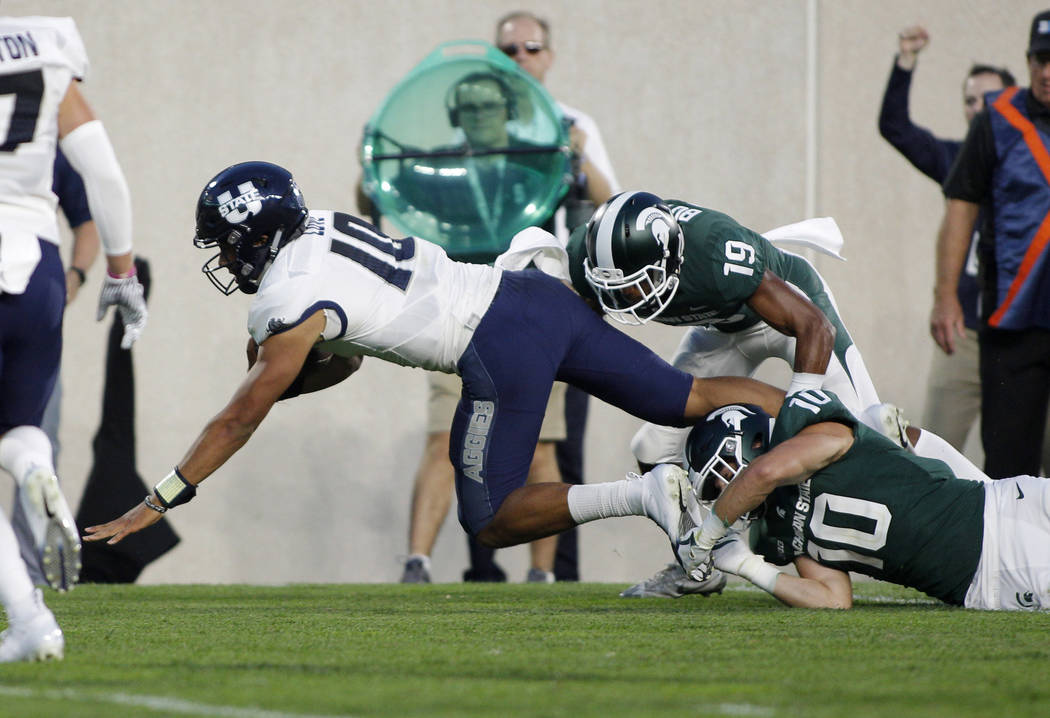 Utah State quarterback Jordan Love, left, is tripped by Michigan State's Matt Morrissey (10) and Josh Butler (19) during the second quarter of an NCAA college football game, Friday, Aug. 31, 2018, ...
