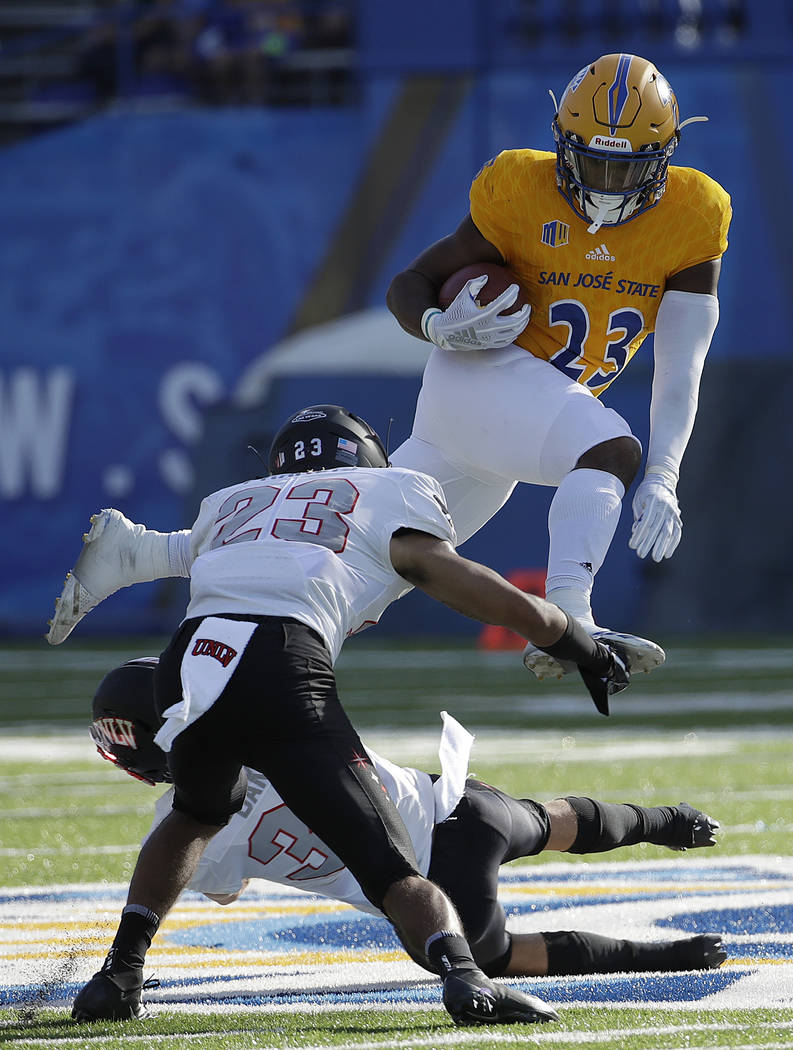 San Jose State running back Tyler Nevens, top, runs against UNLV defensive backs Greg Francis (23) and Dalton Baker during the first half of an NCAA college football game in San Jose, Calif., Satu ...