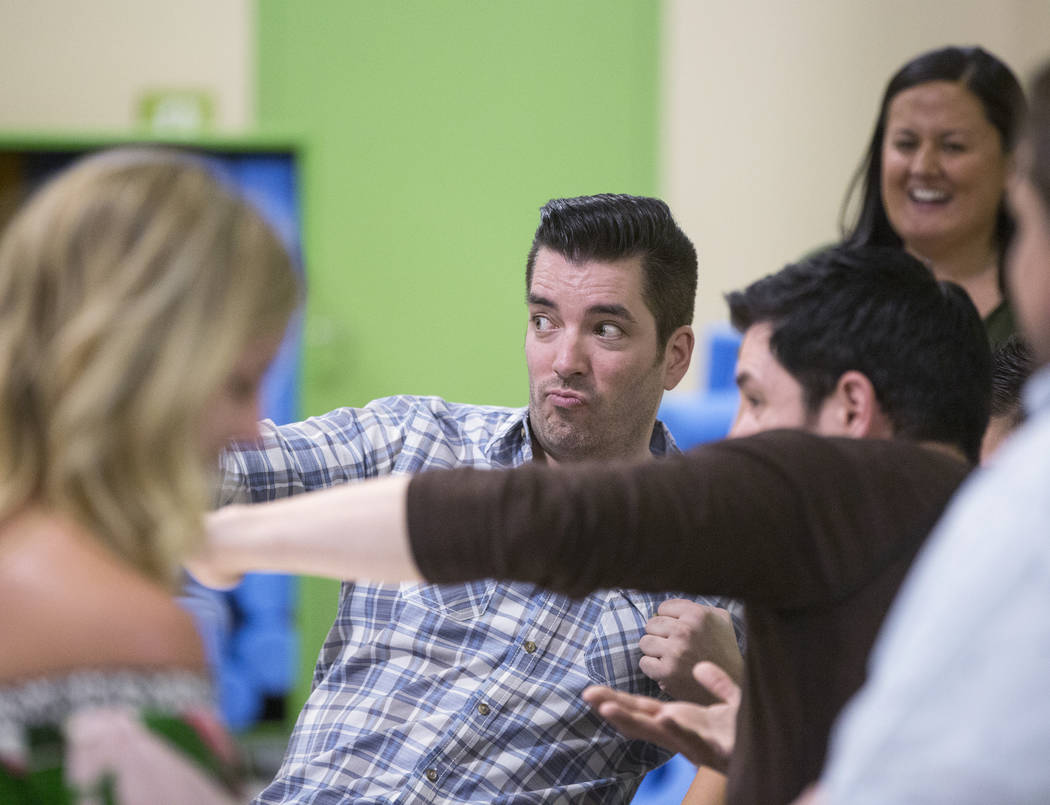 """Jonathan, middle, and Drew Scott of """"Property Brothers"""" joke around with fans during a book signing at Discovery Children's Museum on Monday, Oct. 8, 2018, in Las Vegas. Benjamin Hager L ..."""
