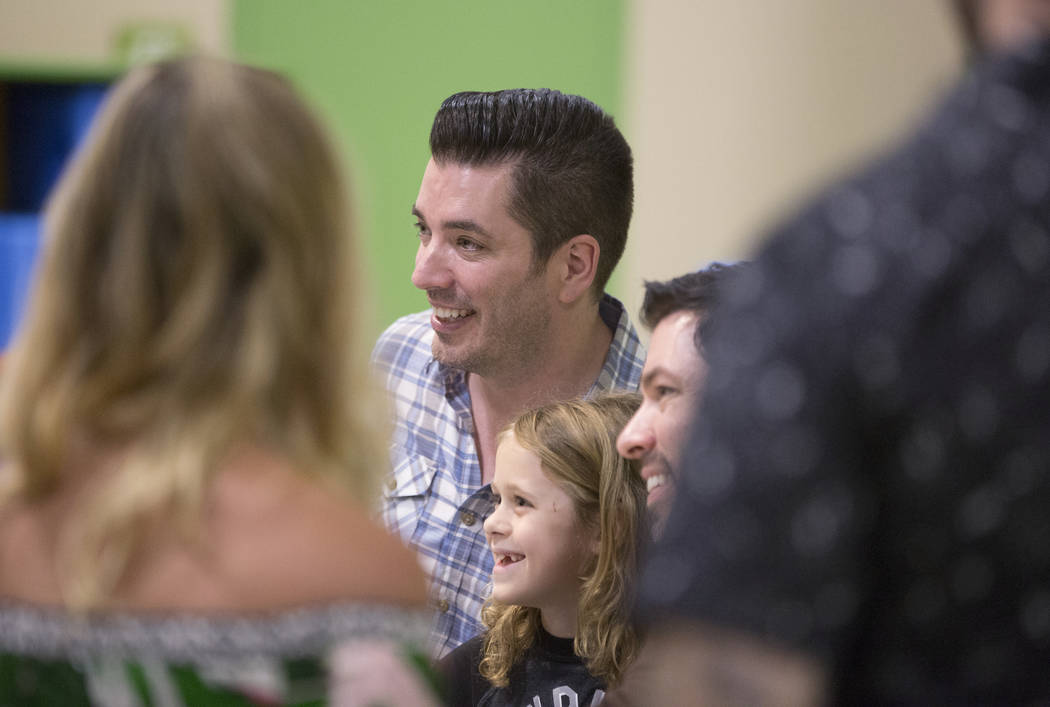 """Jonathan, middle, and Drew Scott of """"Property Brothers"""" take a photo with Dominic Kleckner, 7, during a book signing at Discovery Children's Museum on Monday, Oct. 8, 2018, in Las Vegas. ..."""