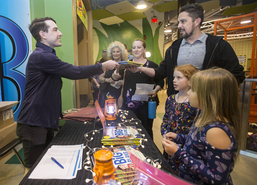 """Drew Cohen, left, hands a copy of Jonathan and Drew Scott's new children's book """"Builder Brothers Big Plans"""" to Sia Mozaffarimehr during a book signing at Discovery Children's Museum on ..."""