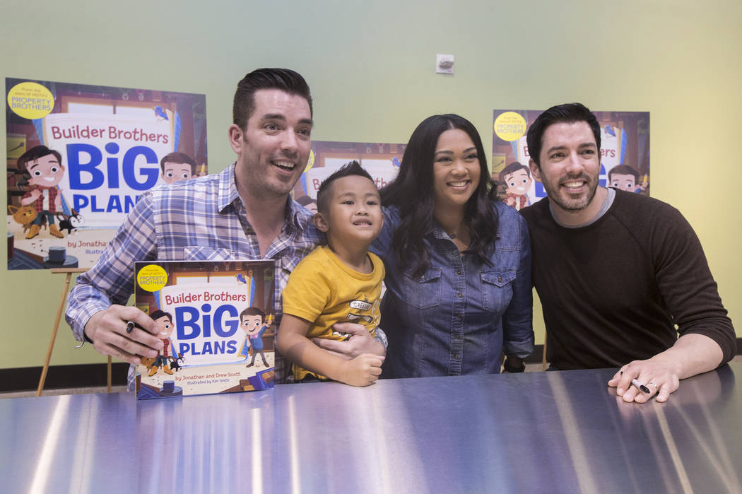 """Jonathan, left, and Drew Scott of """"Property Brothers"""" take a photo with Lynn Halili and her son Kai, 5, during a book signing at Discovery Children's Museum on Monday, Oct. 8, 2018, in L ..."""