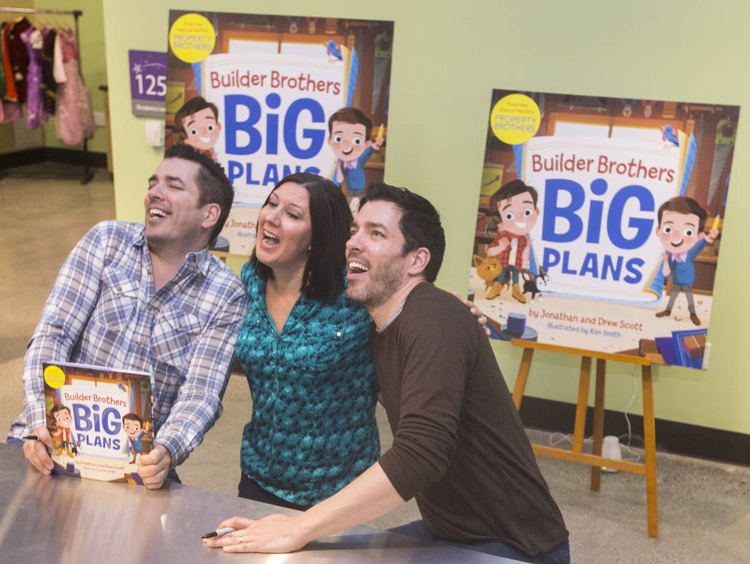 """Jonathan, left, and Drew Scott of """"Property Brothers"""" joke around with Michelle Krance during a book signing at Discovery Children's Museum on Monday, Oct. 8, 2018, in Las Vegas. Benjami ..."""
