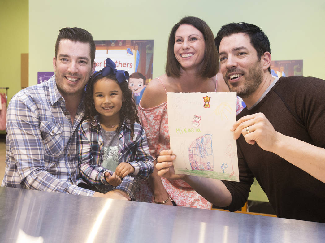 """Jonathan, left, and Drew Scott of """"Property Brothers"""" take a photo with Tara Kona and her daughter Mikaela, 5, during a book signing at Discovery Children's Museum on Monday, Oct. 8, 201 ..."""