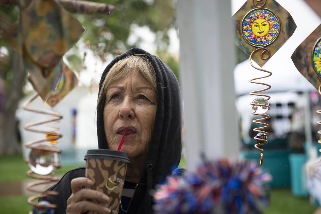 Jeanne Wadsworth of Las Vegas looks at the artworks being sold at the Brighten Your Life Creations tent, a business from Oxnard, California, at the annual Art in the Park event in Boulder City, Su ...