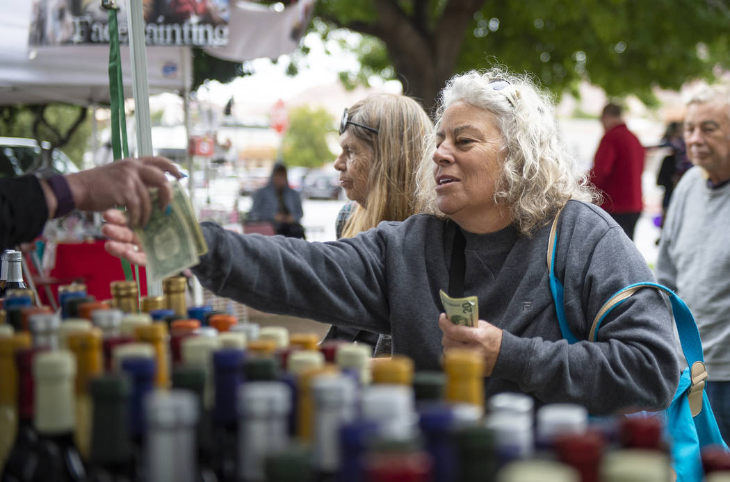 Nancy Dineen of Huntington Beach, California hands money to Arlene Harris, an owner at California Balsamic, as she buys one of the items for sale at the California Balsamic tent at the annual Art ...