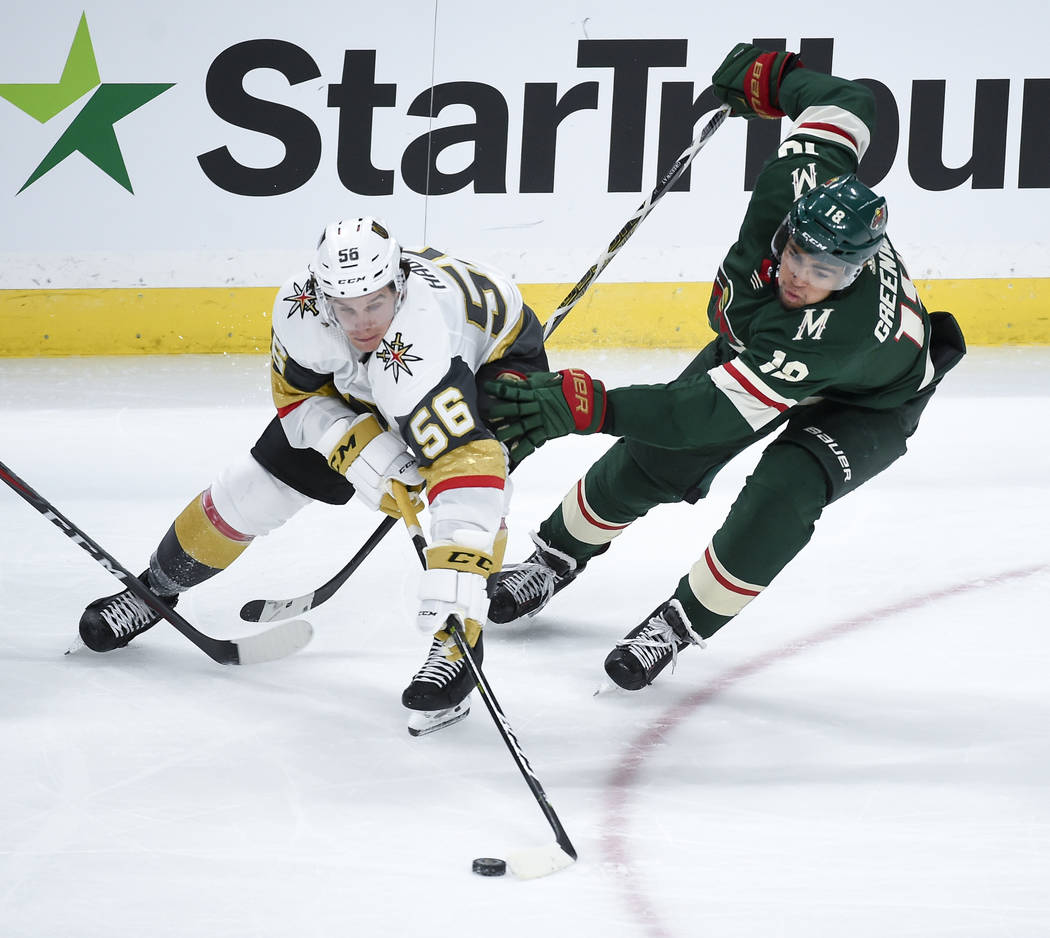Vegas Golden Knights left wing Erik Haula (56) and Minnesota Wild left wing Jordan Greenway (18) battle for the puck in the third period during an NHL hockey game Saturday, Oct. 6, 2018, in St. Pa ...