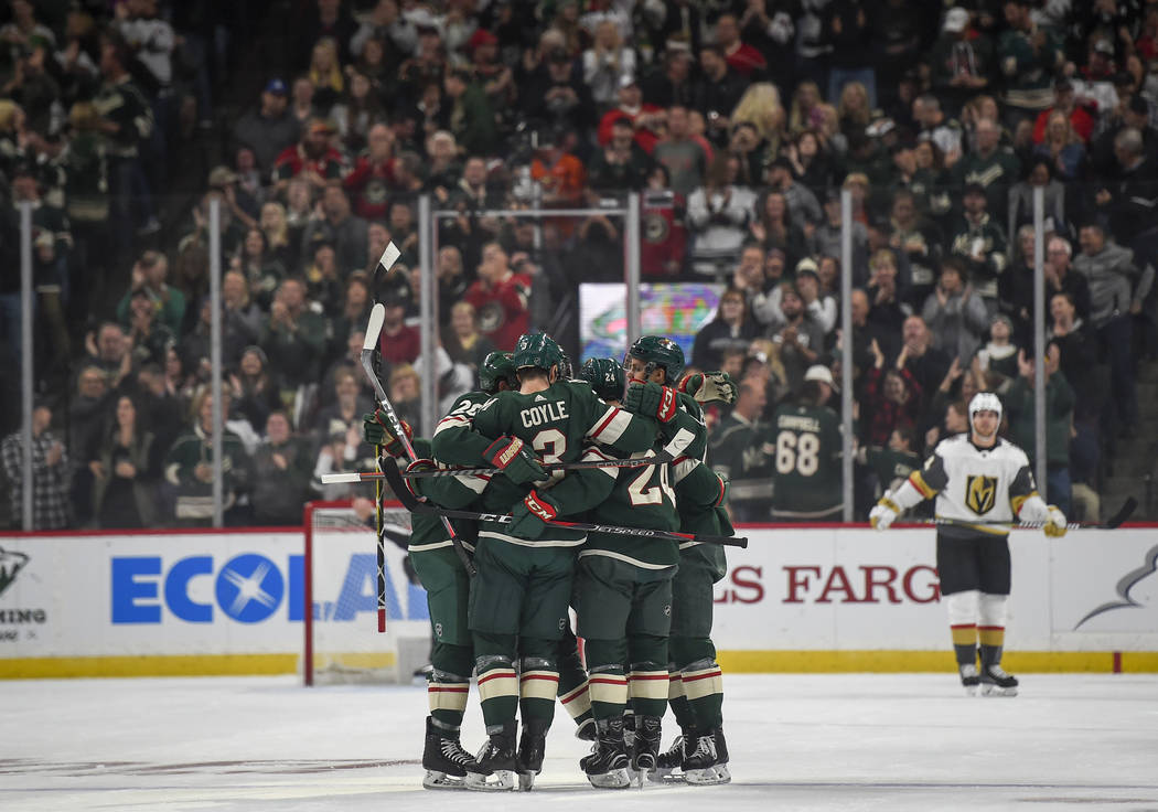 The Minnesota Wild celebrate after defenseman Mathew Dumba scored the first goal of the home opener against the Vegas Golden Knights in the first period during an NHL hockey game Saturday, Oct. 6, ...