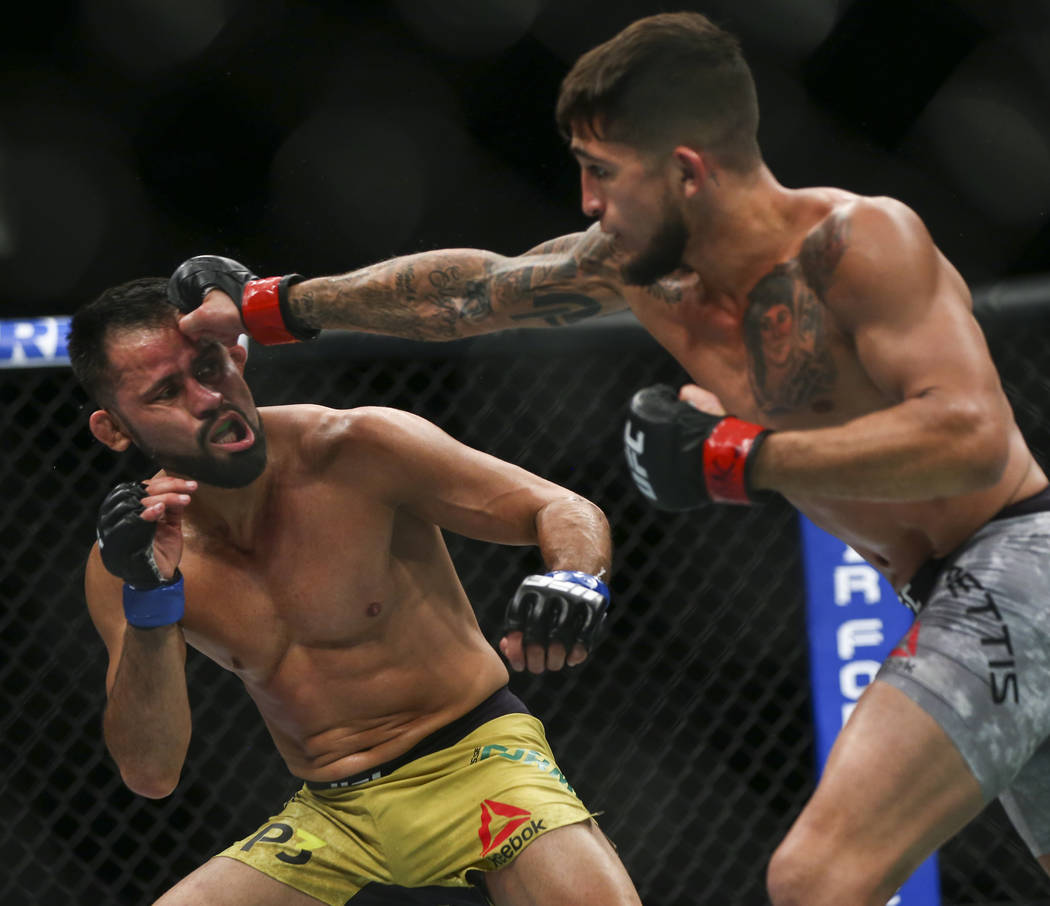 Jussier Formiga, left, takes a hit from Sergio Pettis during their flyweight bout at UFC 229 at T-Mobile Arena in Las Vegas on Saturday, Oct. 6, 2018. Chase Stevens Las Vegas Review-Journal @csste ...