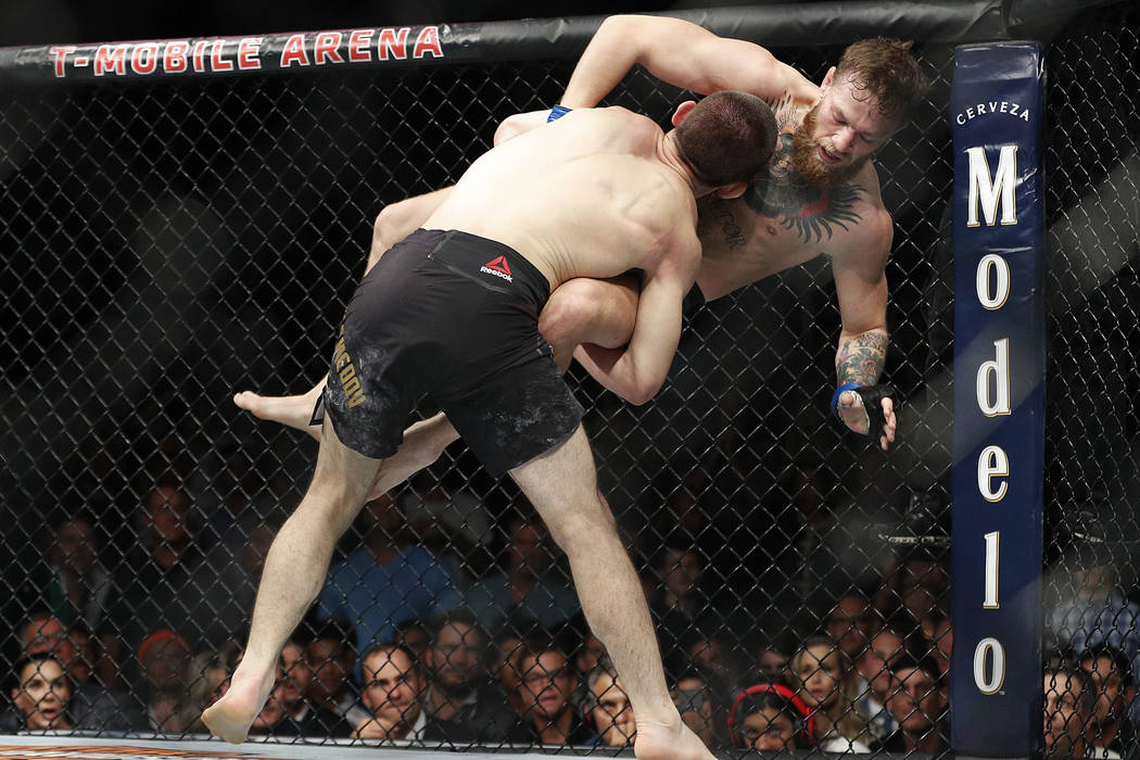 Khabib Nurmagomedov, left, takes down Conor McGregor during a lightweight title mixed martial arts bout at UFC 229 in Las Vegas, Saturday, Oct. 6, 2018. (AP Photo/John Locher)