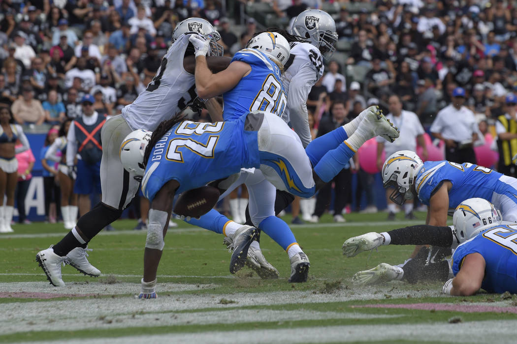 Los Angeles Chargers running back Melvin Gordon, center, scores a touchdown during the first half of an NFL football game against the Oakland Raiders Sunday, Oct. 7, 2018, in Carson, Calif. (AP Ph ...